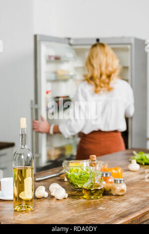 selective focus of mature woman taking something from fridge in kitchen, vegetables and wine on tabletop - Stock Photo