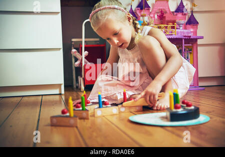 Girl placing toy cake pieces on the floor in her bedroom. Horizontal indoors shot. - Stock Photo