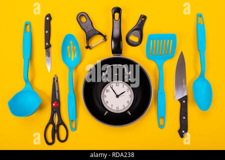 Close up portrait of frying pan with set of kitchen utensils on yellow background - Stock Photo