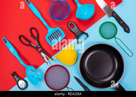 Close up portrait of frying pan with set of kitchen utensils on red-blue background - Stock Photo