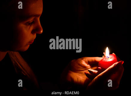 The girl in the dark looking at a lighted candle - Stock Photo