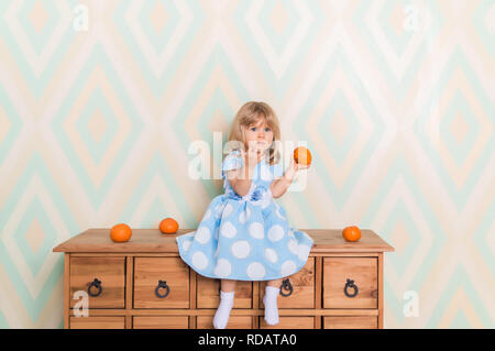 Toddler child baby girl in light blue dress sitting on the wooden chest of drawers seriously looking furrowing brows and holding fresh orange mandarins in left hand on rhomb wallpaper background - Stock Photo