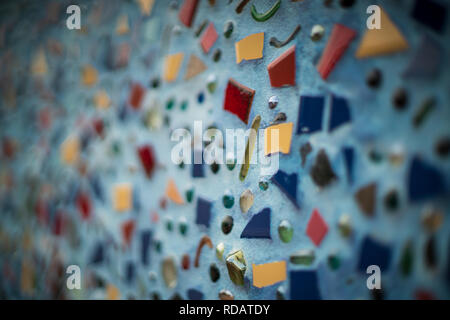 Art mosaic with broken tile pieces attached to wall. - Stock Photo