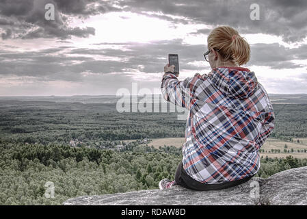Long hair cute girl take picture by smart phone. Morning hilly landscapewith few clouds of mist. - Stock Photo