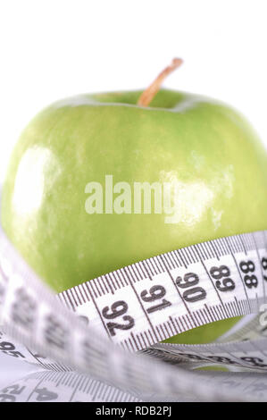 A green apple surrounded with measurement tape on white - Stock Photo