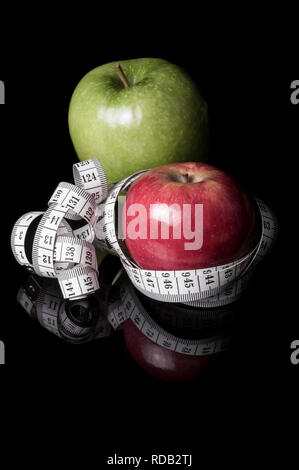 Red and green apples surrounded by measurement tapeline on black with reflection - Stock Photo