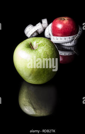 Red and green apples surrounded by measurement tapeline on black - Stock Photo