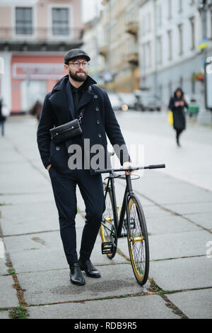 A young smiling stylish businessman pushing a bicycle while going to work. - Stock Photo