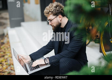 Portrait of young handsome bearded man looking aside using laptop computer with bicycle outdoors.