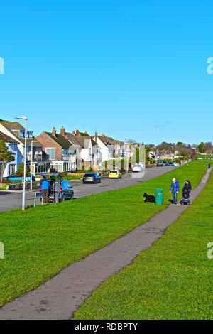 A young family with dog & pushchair walking along the cliff top path at Penarth, Cardiff, S.Wales. Expensive detached houses overlook the sea. - Stock Photo
