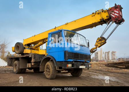 Mobile Crane on a road and tower crane in construction site - Stock Photo