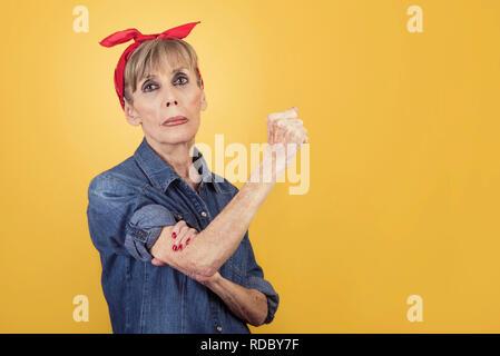 senior woman expressing women power on a yellow background - Stock Photo