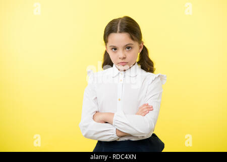 Disagreement and stubbornness. Girl school uniform serious face offended yellow background. Kid unhappy looks strictly. Girl folded arms on chest looks serious. Sensitive girl not want to talk. - Stock Photo