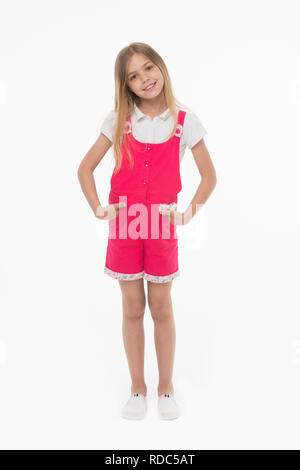 Girl wearing hot pink jumpsuit, white blouse and shoes. Cheerful kid in summer outfit, vacation concept. Child holding hands in pockets. Lovely girl with long blond hair isolated on white background. - Stock Photo