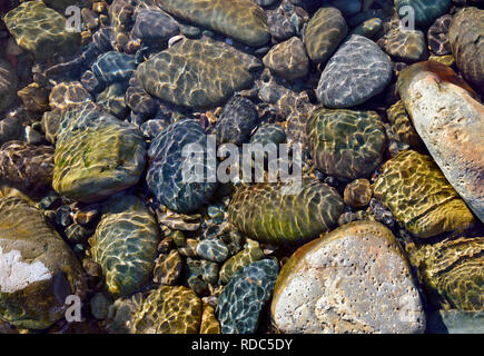 A close up view of submerged rocks in a rock pool on Barmouth Beach, Wales. - Stock Photo