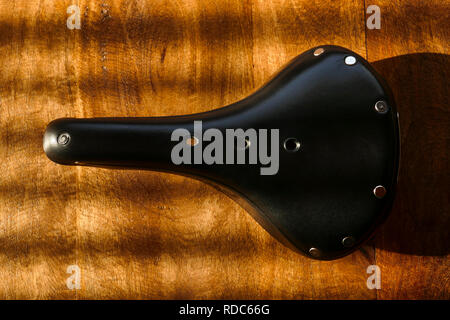 Brooks B17 standard black leather bicycle saddle on wooden table, top view - Stock Photo
