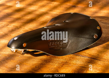 Brooks B17 standard black leather bicycle saddle on wooden table, side view - Stock Photo
