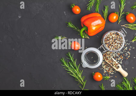 Black, purple, and white rice (Oryza sativa) mix in glass jar on black stone concrete textured surface background. Raw pepper, tomatoes, olive oil and - Stock Photo