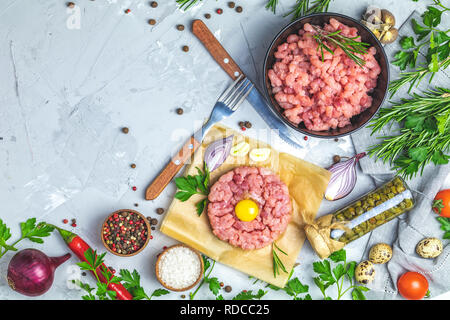 Healthy food, cooking concept. Homemade raw organic minced beef meat and steak tartare with yolk with vegetables on light gray stone concrete textured - Stock Photo