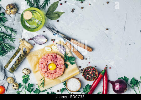 Steak tartare with yolk and set of cutlery knife and fork on light gray stone concrete textured surface background with ingredients for making. Copy s - Stock Photo