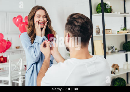 back view of man doing proposal at valentines day to girlfriend - Stock Photo