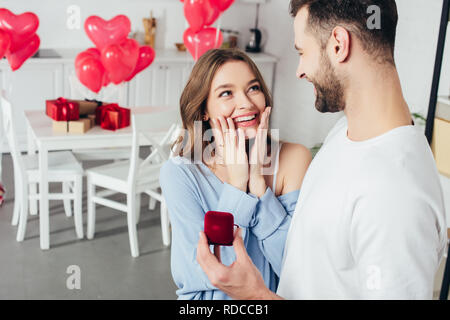 selective focus of surprised girl touching face while man doing proposal at valentines day - Stock Photo
