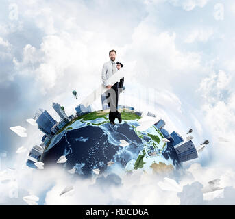 Ambitious and young businessman in suit pointing aside by means of big white arrow in hands while standing on Earth globe with sky view on background. - Stock Photo