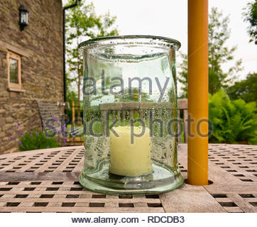 a large white unlit candle inside a glass jar covered with rain drops on a wooden patio table uk - Stock Photo