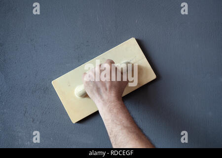 Hand with plastic trowel plastering and smoothing a wet concrete plastered wall. - Stock Photo