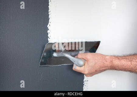 Hand with a trowel plastering a wall with decorative plaster - Stock Photo