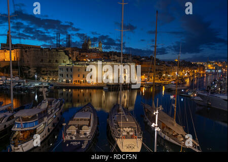 View across the harbour from Vittoriosa to Senglea at dusk with yachts moored. - Stock Photo