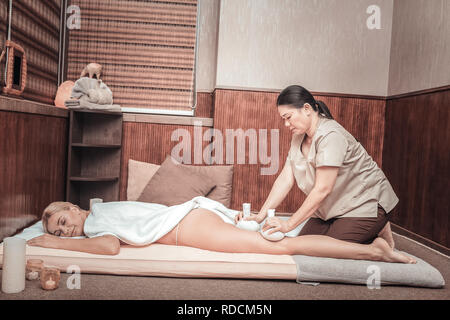 Nice skilled masseuse massaging her clients body - Stock Photo