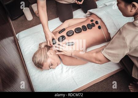 Professional Asian masseuses putting hot stones on female back - Stock Photo
