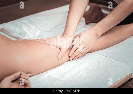 Professional female masseuse touching her clients leg - Stock Photo