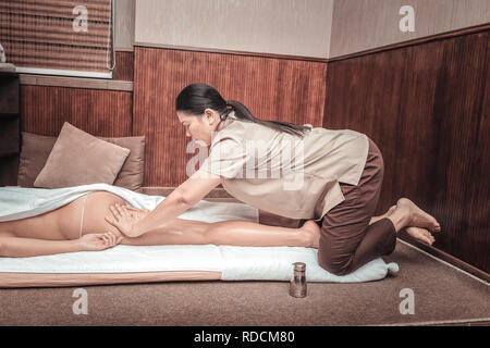 Serious female masseuse massaging her clients body - Stock Photo