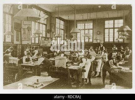 Edwardian postcard of boys drawing plans for woodwork in a classroom, circa 1910, U.K - Stock Photo