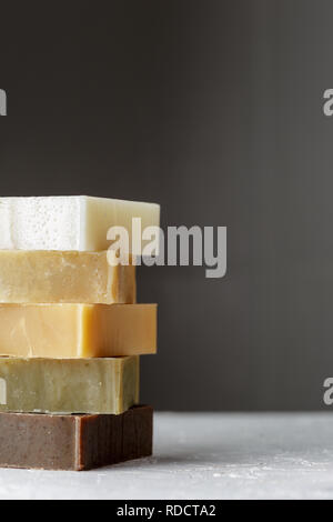 Tower stack of different kinds of handmade soaps over grey background - Stock Photo