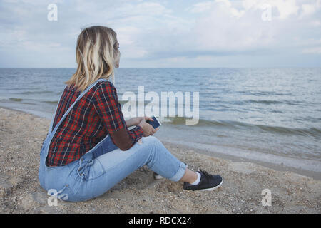 beautiful blonde girl sits on the beach and looks at the sea Toned - Stock Photo