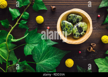 Polished Nephrite Jade with Ivy and Craspedia on Dark Wood - Stock Photo