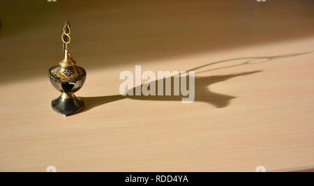 Magic genie lamp with shadows on a light background. Magic Aladdin's genie lamp - Stock Photo
