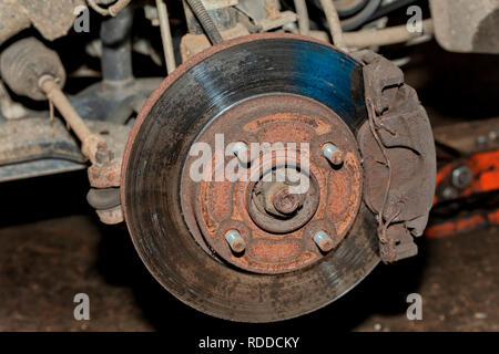 A car with the front wheel removed where you can see the brake disc. - Stock Photo