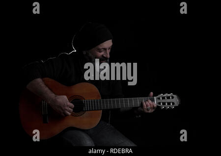 bearded man plays the guitar on stage - Stock Photo