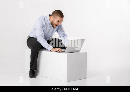 young handsome man in shirt and tie using laptop - Stock Photo