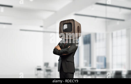 Cropped image of businessman in suit with old TV instead of head keeping arms crossed while standing inside office building. - Stock Photo