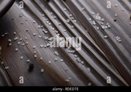 Salt crystals on rustic wooden kitchen table - Stock Photo