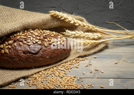 Bread with sunflowers seeds, fresh raw wheat seeds and ear of ripe wheat on rustic wooden table - Stock Photo