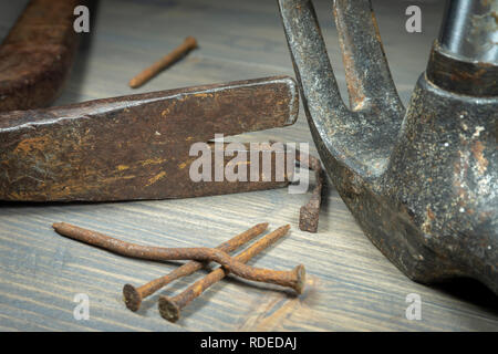 Old rusty nails with two claw hammers in a close up cropped view in a maintenance, repair, construction or DIY concept - Stock Photo
