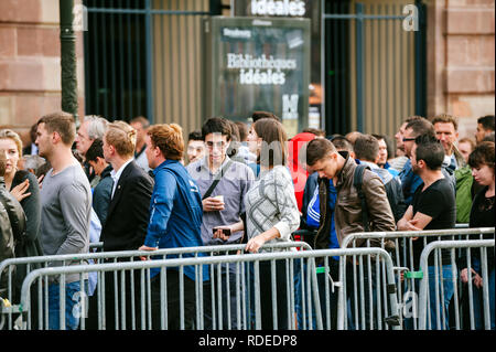 STRASBOURG, FRANCE - SEP, 19 2014: Large queue in front of Apple Store with customers waiting in line to buy the latest iPhone iPad Apple Watch and notebook - Stock Photo