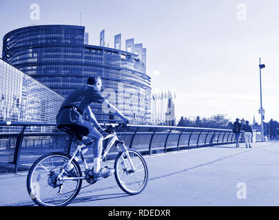 STRASBOURG, FRANCE - AUG 20, 2016: Blue color toned chromacity of senior cyclist sport workout in front of the european parliament building in Strasbourg on a calm summer day