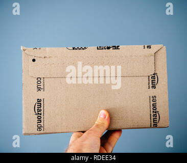 PARIS, FRANCE - APR 24, 2018: Man holding rear part of the Amazon Prime cardboard delivery box against gray background - on-line e-commerce shopping - Stock Photo